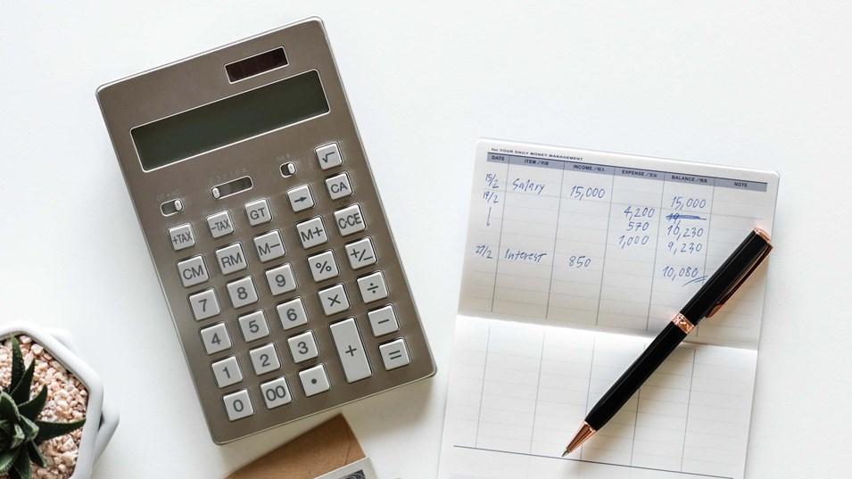 kalkulator og papirbokk med penn